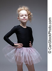 Studio shot of adorable little dancer posing on gray...