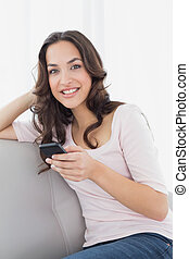 Smiling young woman text messaging on sofa at home -...