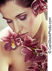 Beautiful young woman with orchid flowers on light...