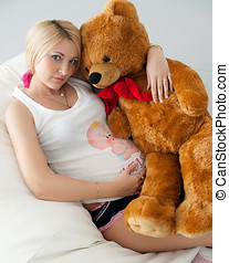 pregnant girl hugging a teddy bear