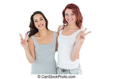 Portrait of two young female friends gesturing peace sign...