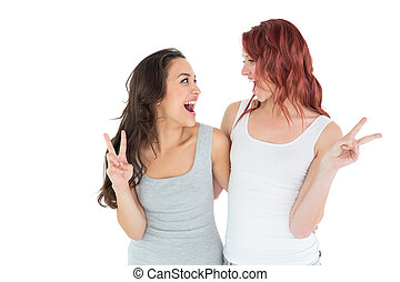Two cheerful female friends gesturing peace sign over white...