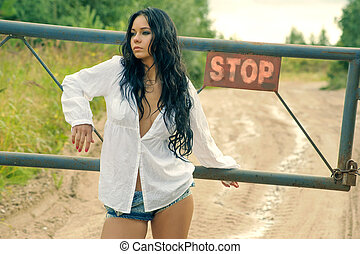 Girl in mini denim shorts standing at the turnpike on a...