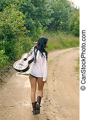 Sexy girl with guitar, standing on a countryside road