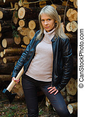 Young pretty woman with huge axe in the forestry