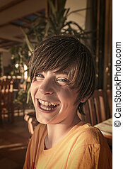 laughing teenager boy sitting in a restaurant.