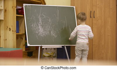 Little boy drawing on a chalkboard at kindergarten - Little...