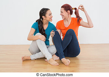 Friends with house keys sitting on the floor - Two cheerful...