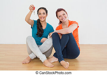 Female friends with house keys sitting on the floor -...