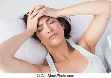 Sleepy woman suffering from headache in bed - High angle...