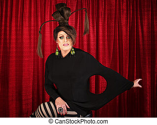 Unique Drag Queen Sitting - Grinning man in drag with unique...