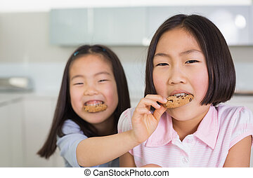 Girl feeding her elder sister a cookies in kitchen