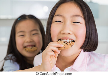 Little girl feeding her elder sister a cookies in kitchen