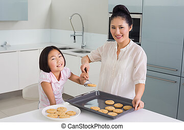 Girl helping her mother prepare cookies in kitchen -...
