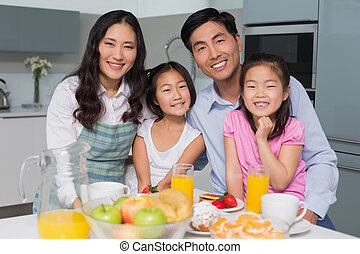Cheerful family of four enjoying healthy breakfast in...