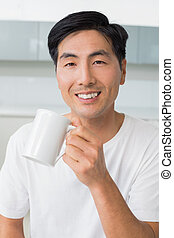 Portrait of a smiling young man drinking coffee in kitchen