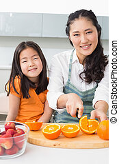 Woman with her young daughter cutting fruit in kitchen