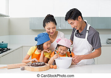 Happy family of four preparing cookies in kitchen - Happy...