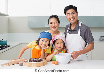 Family of four preparing cookies in kitchen - Portrait of a...