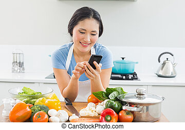Woman text messaging in front of vegetables in kitchen -...