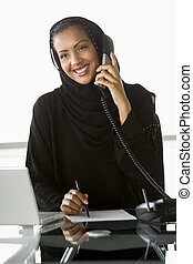 Businesswoman in office by laptop on telephone smiling (high key/selective focus)
