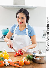 Smiling woman chopping vegetables in kitchen - Portrait of a...