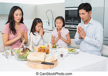 Family of four saying grace before meal in kitchen - Family...