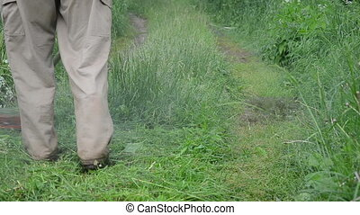 closeup worker mow grass