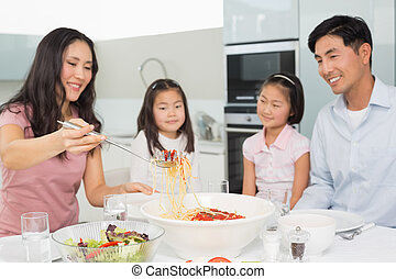 Happy woman serving spaghetti for the family in kitchen