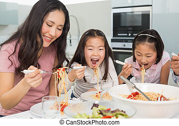 Woman with kids enjoying spaghetti lunch in kitchen - Woman...