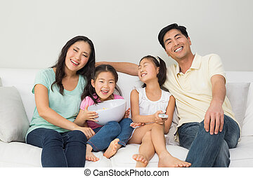Happy family of four watching tv in living room - Portrait...