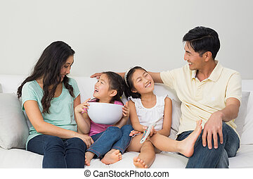 Happy family of with remote control and bowl sitting on sofa...