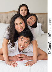 Cheerful family of four lying over each other in bed -...