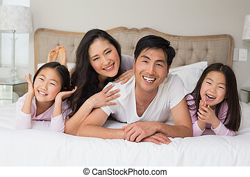 Cheerful family of four lying in bed - Portrait of a...