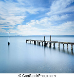 Wooden pier or jetty remains on a blue lake. Long Exposure.