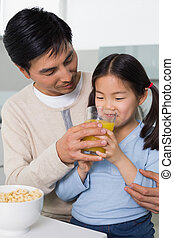 Father with young daughter having breakfast