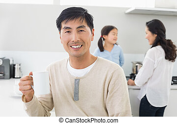 Smiling man holding coffee cup with family in background -...