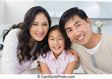 Portrait of a smiling couple with a daughter in kitchen -...