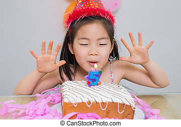 Cute little girl blowing her birthday cake - Close-up of a...