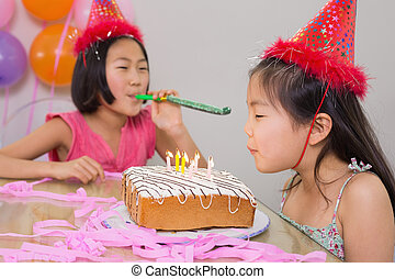 Girls blowing noisemaker and birthday candles - Girl blowing...