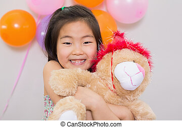 Cute girl hugging soft toy at a birthday party - Close-up...