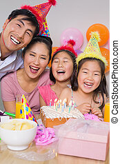 Cheerful family with cake and gifts at a birthday party -...