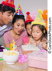 Family blowing cake at a birthday party - Family of four...