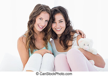 Female friends sitting on bed with arm around - Portrait of...