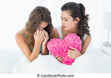 Woman consoling a crying female friend in bed - Young woman...