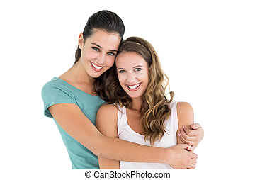Portrait of a young female embracing her friend over white...