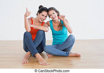 Friends gesturing thumbs up with keys on the floor -...