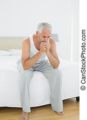 Thoughtful mature man sitting in bed - Full length of a...