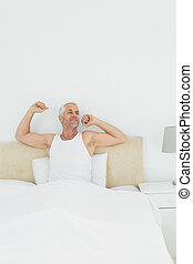 Mature smiling man stretching arms in bed