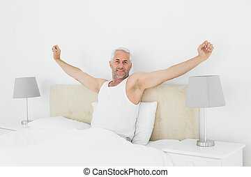 Mature smiling man stretching his arms in bed